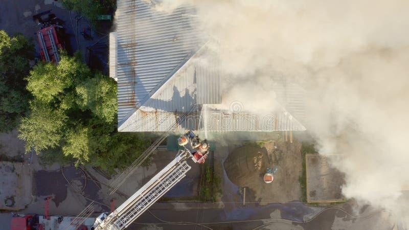 Toit brûlant d'un gratte-ciel résidentiel, nuages de fumée du feu Les sapeurs-pompiers s'?teignent le feu dessus photos stock