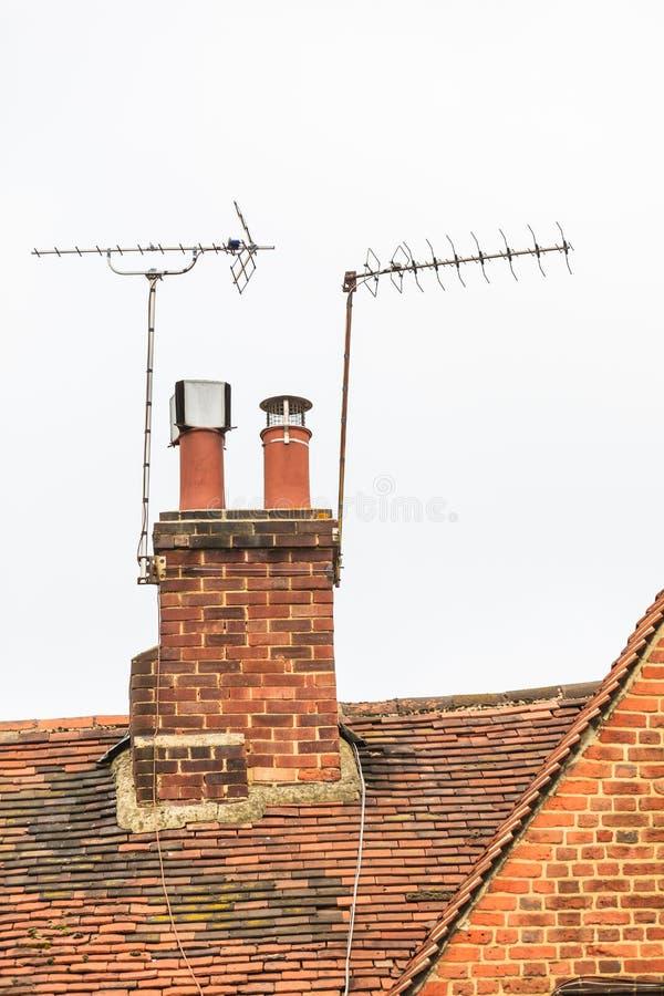 Toit de brique rouge avec la vieilles cheminée et antennes photo stock