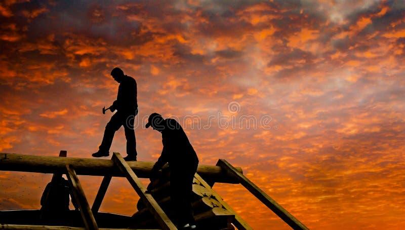 Toit de carlingue de construction de Roofers au crépuscule photographie stock libre de droits