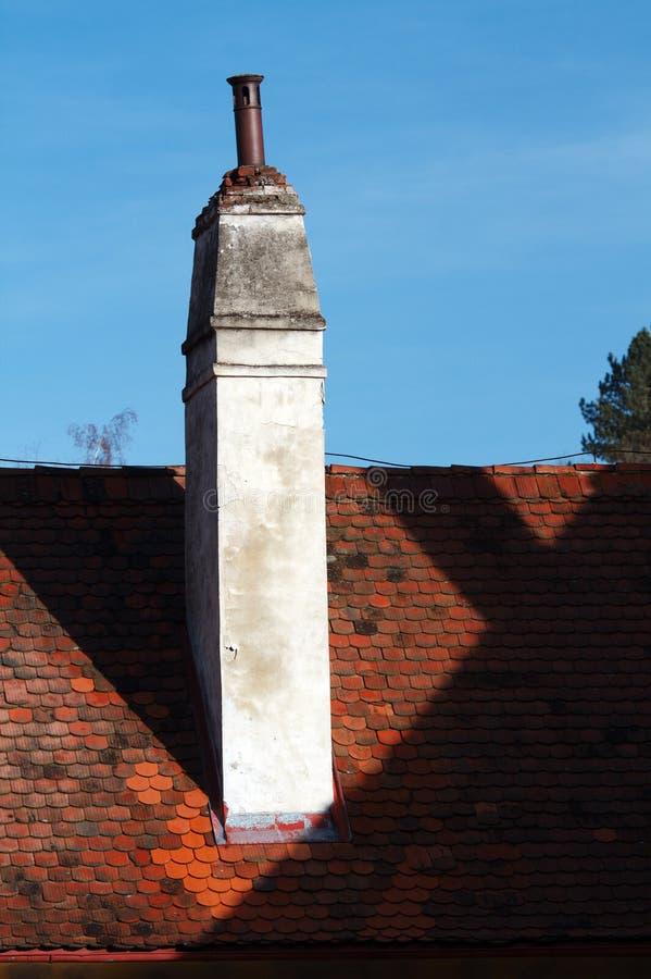Toit de tuile rouge avec la cheminée sur le fond de ciel bleu images stock