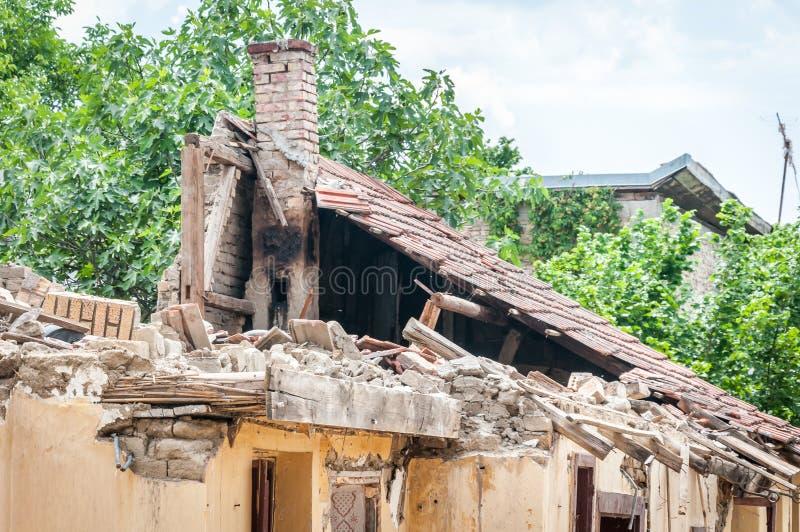 Toit effondré endommagé et cassé de la maison abandonnée après le feu de la bombe de grenade avec les tuiles et le fond déprimé d photo libre de droits