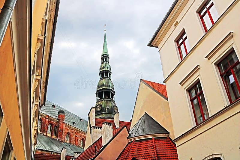 Toits des bâtiments dans la vieille ville et vue supérieure d'église de St Peter St Peter Church, Petrikirche, Riga image libre de droits
