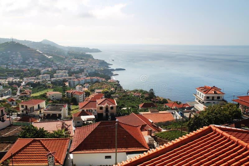 Toits rouges des maisons de la Madère près de l'océan photo stock