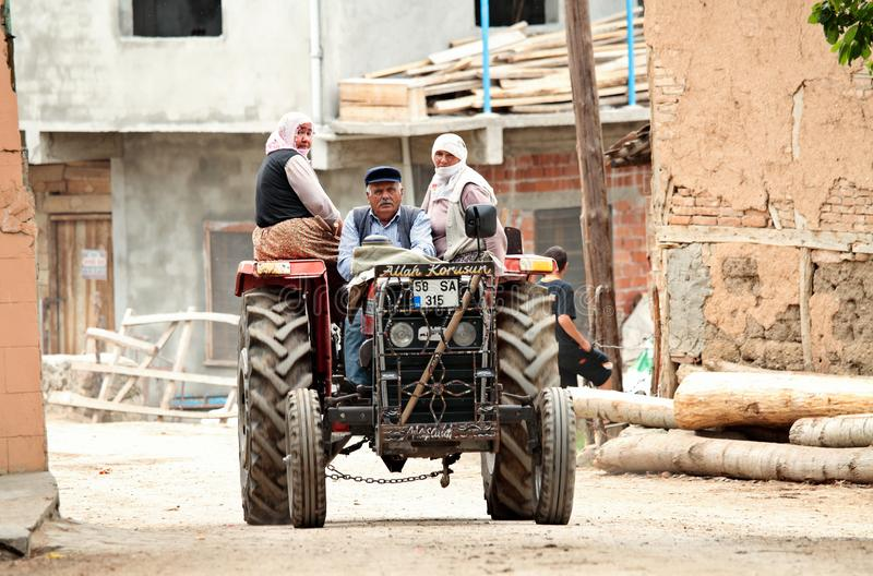 A farmer driving his tractor in the middle of a village. Two women riding with him stock image