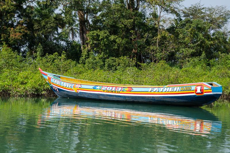 Tokeh Beach, Sierra Leone - January 06, 2014: Beautiful and colorful painted wooden dugout boat moored in mangroves royalty free stock photos