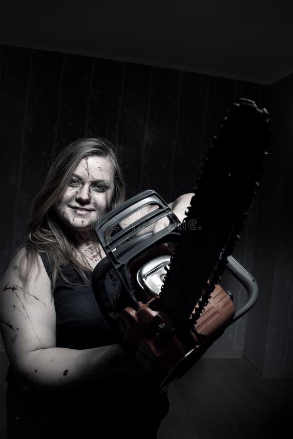 Tokig flicka med chainsawen royaltyfria bilder