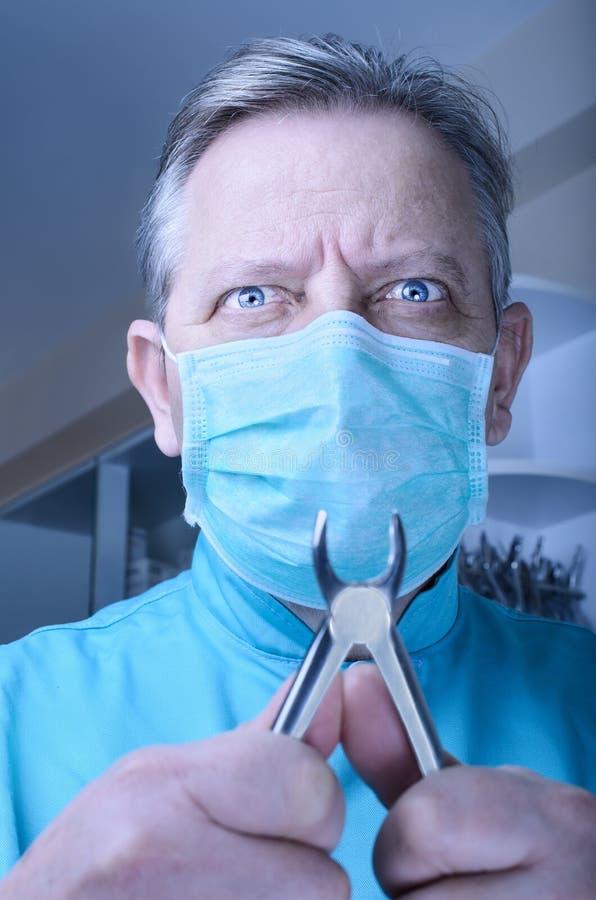 Tokig tandläkare med plattång i hans händer royaltyfria bilder