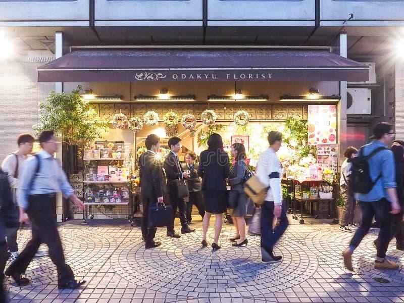 Tokio, Japón - 19 de abril de 2018: grupo de soporte del hombre de negocios delante de la floristería de Odakyu imagenes de archivo