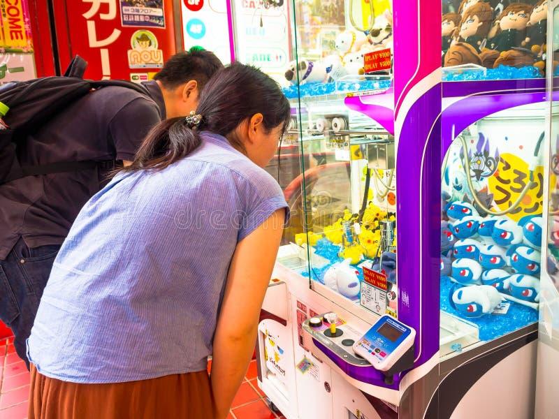 TOKIO, JAPÓN 28 DE JUNIO - 2017: Gente no identificada que mira hola las muñecas clasificadas de Kitty en una máquina de moneda d imágenes de archivo libres de regalías