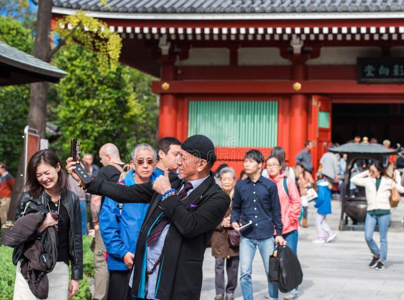 TOKIO, JAPÓN - 7 DE NOVIEMBRE DE 2017: Un hombre elegante hace el selfie en el fondo de una muchedumbre imagenes de archivo