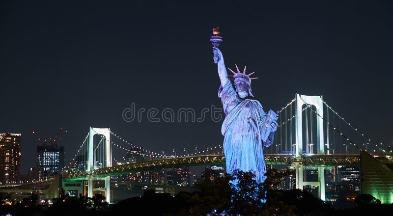 Tokio, Japón 08 29 2017: opinión de la ciudad del nignt en el puente del arco iris y la estatua de Odaiba de la libertad en la is fotos de archivo libres de regalías