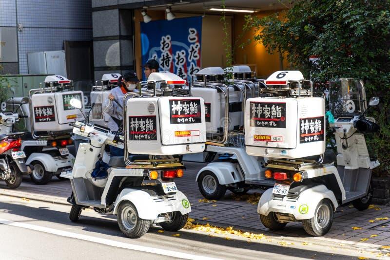 Tokio Japonia, Grudzień, - 25, 2018: Grupa doręczeniowej usługi motocycle lub hulajnoga park przed sklepem gotowym dostarczać jed zdjęcia stock