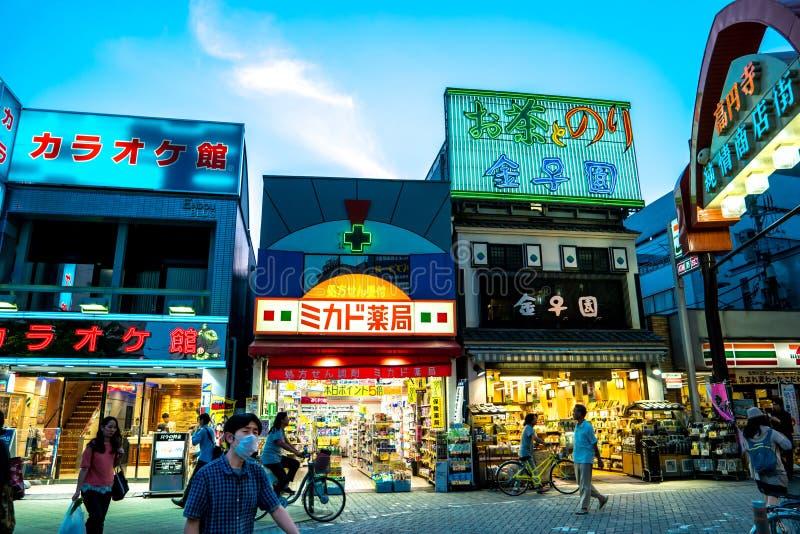 Tokyo - aftongatasikt av Koenji med folk och glödande neonljus arkivfoton