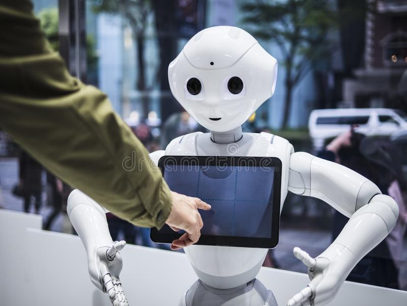 TOKYO GIAPPONE - 16 APRILE 2018: La tecnologia di aiuto di umanoide del touch screen di informazioni del robot del pepe comunica  fotografia stock libera da diritti