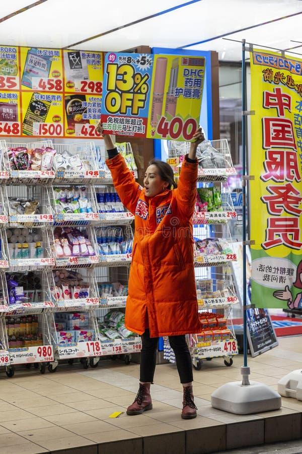 Tokyo, Giappone, 04/08/2017 La ragazza annuncia il negozio nella notte Tokyo immagini stock