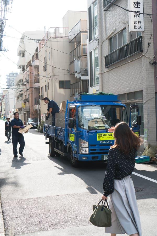 Tokyo, Giappone - 9 ottobre 2018: collettore di immondizia specifico che raccoglie i cartoni mentre una donna che cammina giù la  fotografie stock libere da diritti