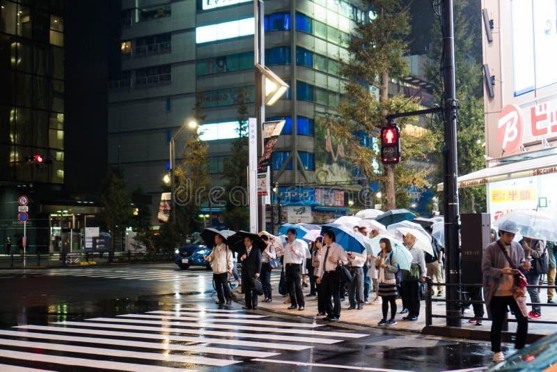 Tokyo, Giappone - 5 ottobre 2018: gli uomini d'affari e le donne hanno aperto i loro ombrelli come la pioggia versa alla notte immagini stock libere da diritti