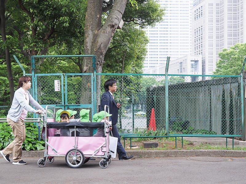 Tokyo Japan - April 22, 2018: barnkammaren tar en unge som loppet med vagnen parkerar in fotografering för bildbyråer