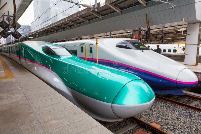 Tokyo, Japan - April 1.2015: De groene E5 Reeksen en de witte E2 Reeksultrasnelle treinen voor Tohoku Shinkansen bij de post van  stock afbeeldingen