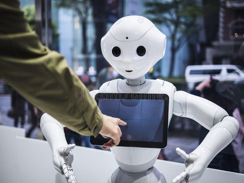 TOKYO JAPAN - APRIL 16, 2018: Teknologi för pekskärmen för information om pepparrobotassistenten meddelar Humanoid med folk i Tok royaltyfri foto