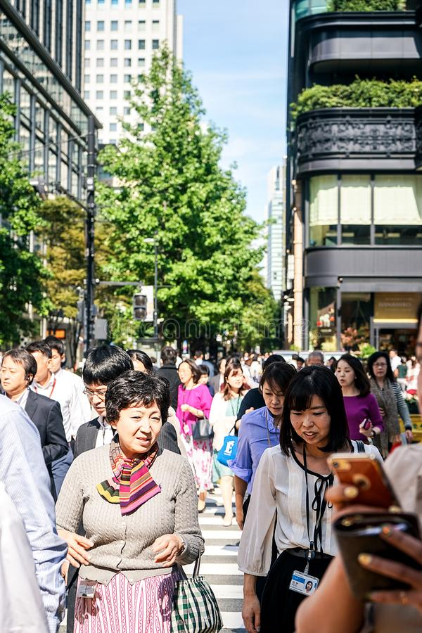 Tokyo, Japan 10.02.2018 crowd of citizens and tourists in business and casual clothes crossing street in popular Ginza district of royalty free stock image