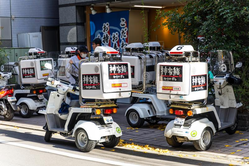 Tokyo, Japan - December 25, 2018: Group of delivery service motocycle or scooter park in front of the store ready to deliver food stock photos