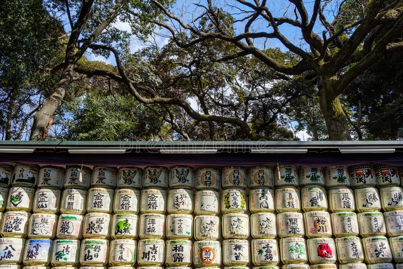 Sake rice barrels piled up with green and red inscriptions in Yoyogi Park. TOKYO, JAPAN - 12 FEB 2018: Sake rice barrels piled up with green and red inscriptions royalty free stock photo