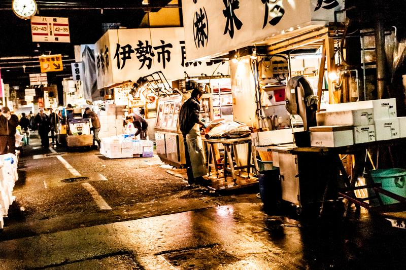 Tokyo, Japan - January 15, 2010: Early morning in Tsukiji Fish Market. Worker laying out fresh fish and seafood on the counter stock photo