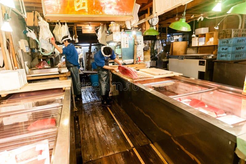Tokyo, Japan - January 15, 2010: Early morning in Tsukiji Fish Market. Workers preparing fresh tuna for sale royalty free stock photos