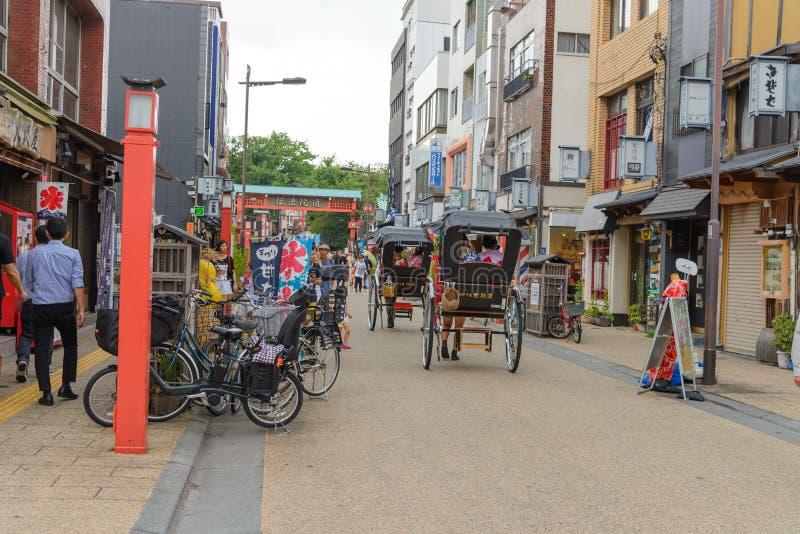 TOKYO, JAPAN JULI 2018: Berühmte richshaws gefahren von tragenden Touristen des Fahrers nahe Senso-jitempel stockbilder