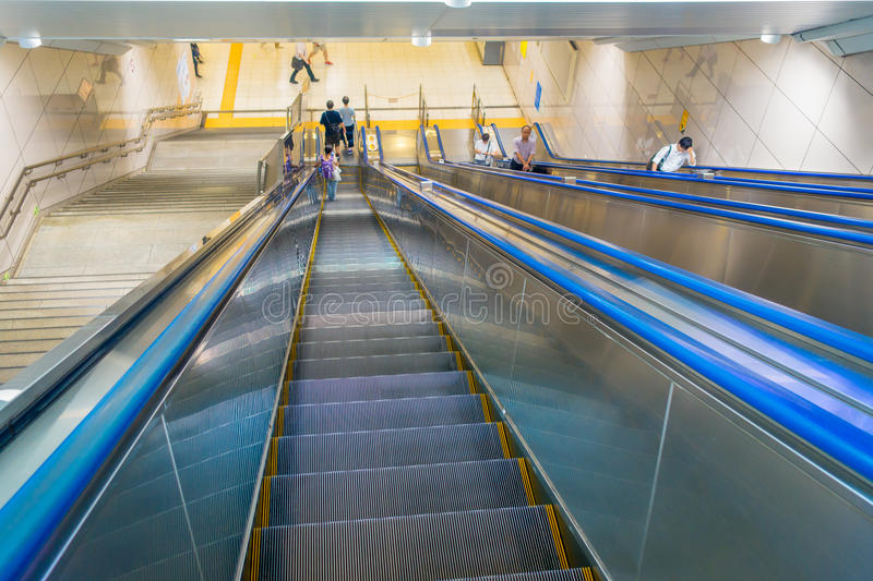 TOKYO, JAPAN JUNE 28 - 2017: Unidentified people walking downstairs and upstairs in electric stairs inside of train stock image