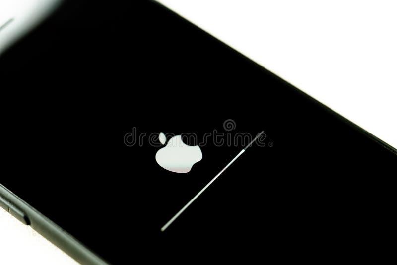 Tokyo Japan - Juni 04 2019: Apple iPhone med iOS-förbättringsskärmen med framstegstången på den vita tabellen royaltyfri bild