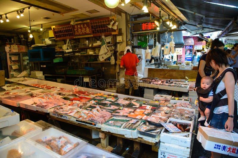 Tokyo Japan - Juni 18, 2015: Köpmanförsäljningsskaldjur i den Tsukiji fisken i Tokyo, Japan Den Tsukiji fiskmarknaden är en av de arkivbilder