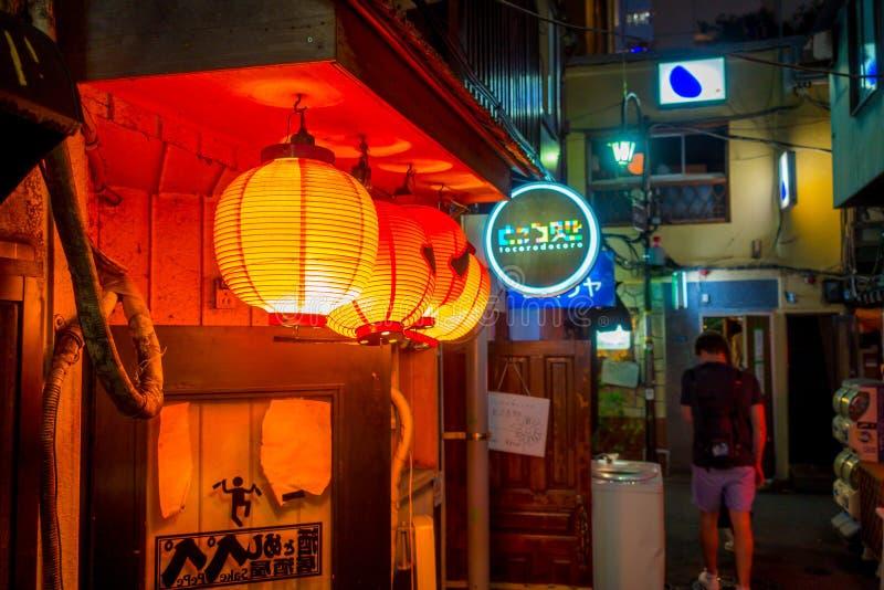TOKYO JAPAN JUNI 28 - 2017: Röda lyktor med Japanesse bokstäver på natten i traditionella bakgatastänger i Shinjuku royaltyfri foto