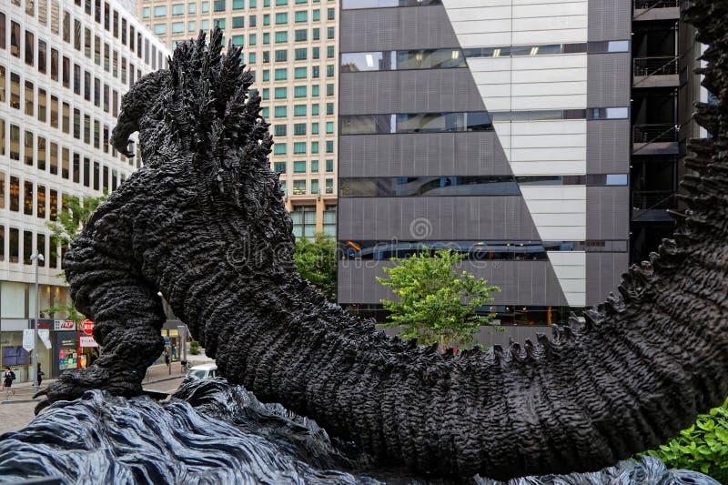 Godzilla sculpture in Hibaya. TOKYO, JAPAN, May 14, 2019 : Godzilla sculpture in Hibaya in front of huge modern buildings royalty free stock photography