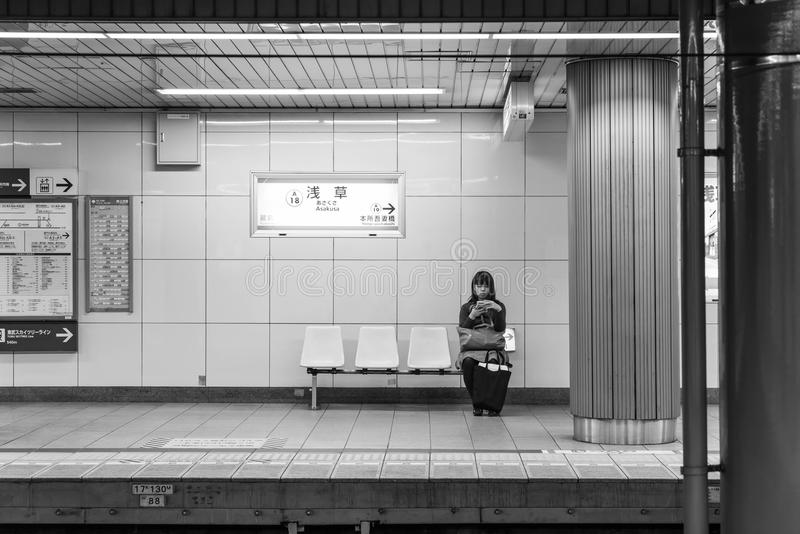 TOKYO, JAPAN - NOV 15, 2016 : Tokyo Metro subway with lady waiting. Tokyo Metro subway is a popular mode of transportation in. Tokyo for people to commute stock photos