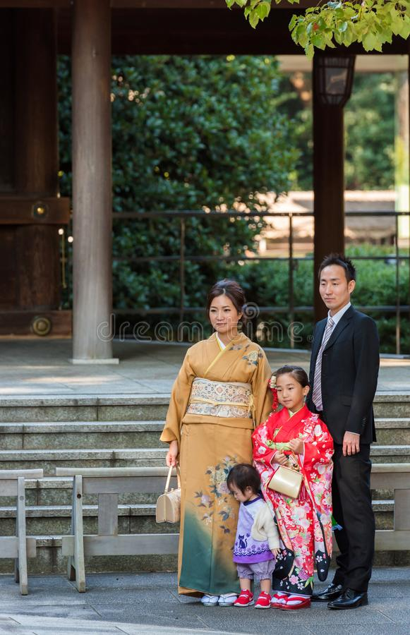 TOKYO, JAPAN - NOVEMBER 7, 2017: A family in a kimono is photographed in a city park. Vertical. TOKYO, JAPAN - NOVEMBER 7, 2017: A family in a kimono is royalty free stock image