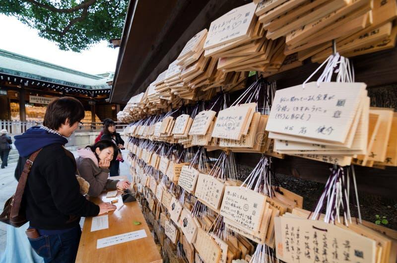 TOKYO JAPAN - NOVEMBER 23, 2013: Folk som skriver Ema Plaques på en Meiji Jingu Shrine royaltyfri foto