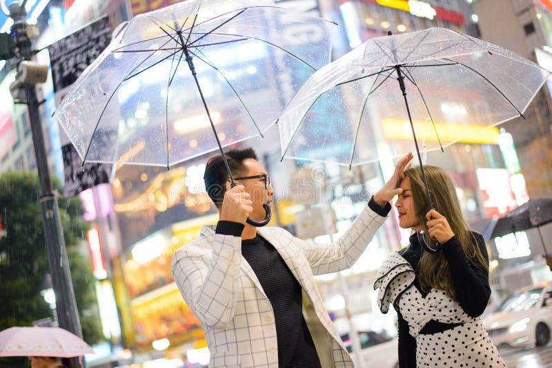 Tokyo Japan - November 13, 2017: Natt som regnar dag på Shibuya med det hållande paraplyet för japanska par royaltyfria foton