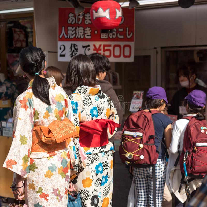 TOKYO, JAPAN - OCTOBER 31, 2017: Two girls in a kimono on a city street. Back view. TOKYO, JAPAN - OCTOBER 31, 2017: Two girls in a kimono on a city street royalty free stock image