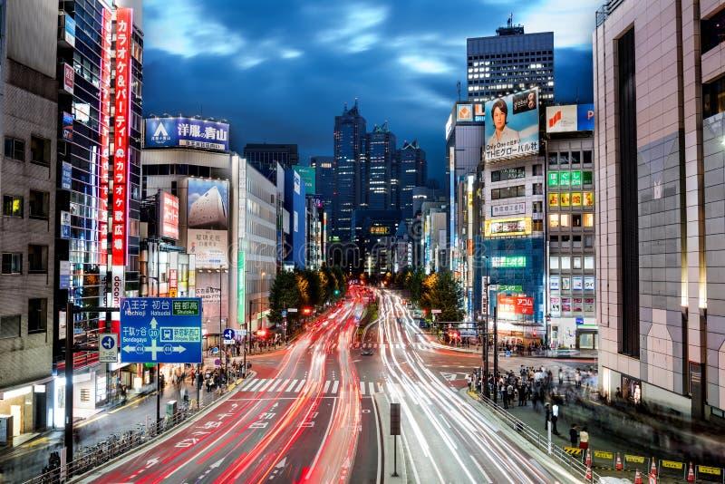Tokyo, Japan - Oktober 16, 2016: Cityscape bij nacht in Shinjuku-District met wolkenkrabbers, snelle verkeer en mensen op de stra stock afbeelding