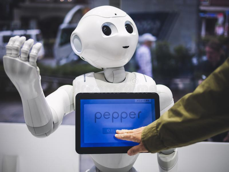 TOKYO, JAPON - 16 AVRIL 2018 : Assistant de humanoïde de robot de poivre avec l'écran de l'information dans le magasin Japon de S photos stock