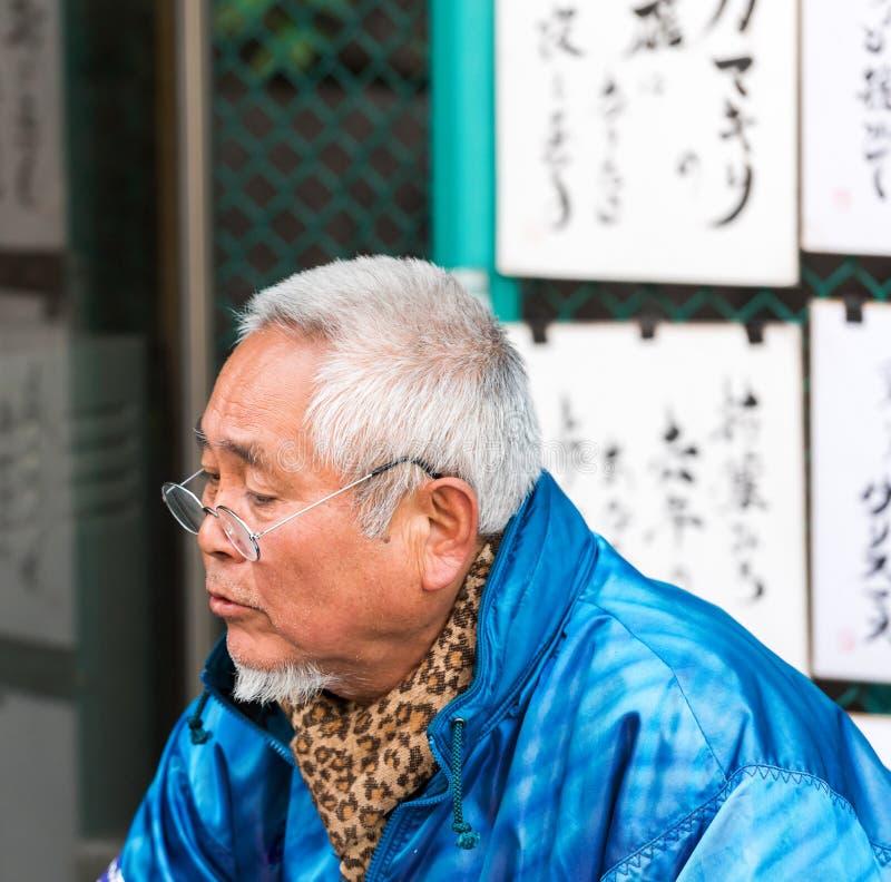 TOKYO, JAPON - 7 NOVEMBRE 2017 : L'homme aux cheveux gris en verres sur une rue de ville Plan rapproché images stock