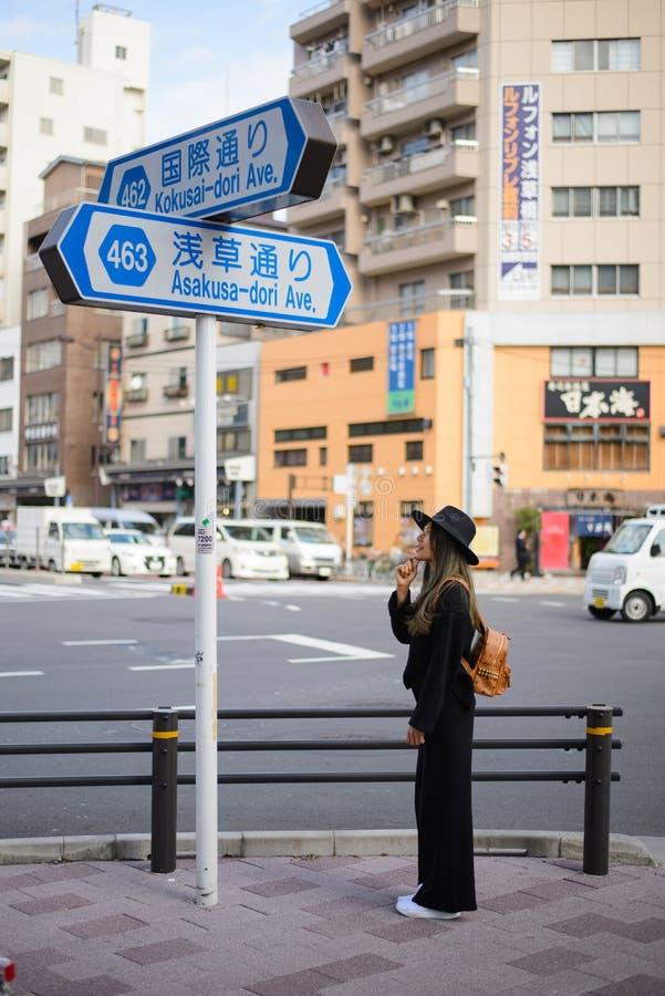TOKYO, JAPON - 13 novembre 2017 : Regard de fille de touristes à la plaque de rue au temple bouddhiste Sensoji, Japon Le temple d photos libres de droits
