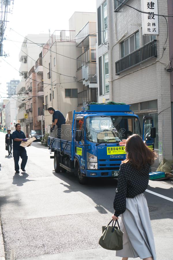 Tokyo, Japon - 9 octobre 2018 : éboueur spécifique rassemblant des cartons tandis qu'une femme descendant la rue photos libres de droits