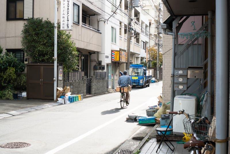 Tokyo, Japon - 9 octobre 2018 : un cycliste livrant des marchandises dans la rue intérieure du Japon photographie stock libre de droits