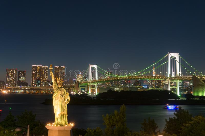 Tokyo nigh cityscape with Rainbow bridge and Statue of Liberty stock photography