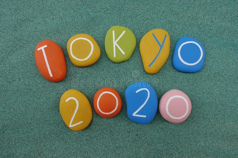 Tokyo 2020, souvenir with colored stones over green sand stock image