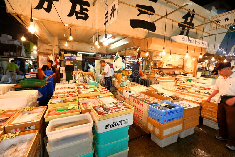Tokyo: Tsukiji Seafood Fish Market. Workers selling fresh seafood at the Tsukiji Wholesale Seafood and Fish Market in Tokyo Japan. Locals and tourist visit the royalty free stock photo