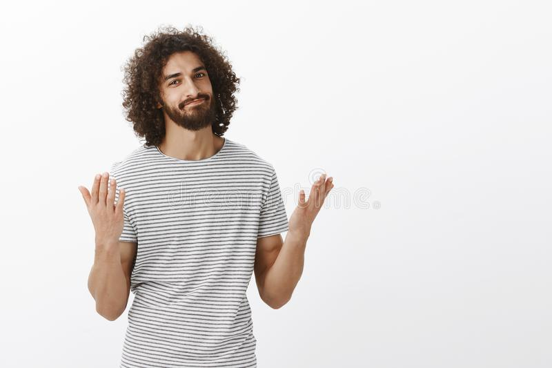 Told you I was right. Handsome eastern male model with beard and curly hair, raising hands and smirking, being relieved. And saying finally, waiting for stock photo